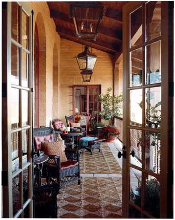 For the upper veranda of a Tuscan-style villa in Santa Ynez, California, Michael S. Smith arranged a collection of black painted Victorian wicker furniture over jute rugs. Photo by François Halard' for Elle Decor.