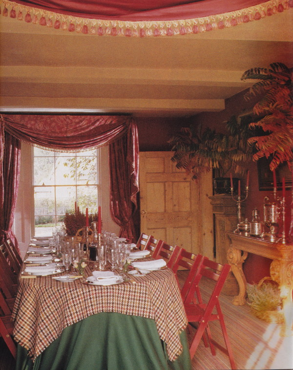Valentino curtains and red painted deck chairs surround a table set for an after hunt lunch with 18th-century French candelabra gifted to Robin Smith-Ryland and his wife, Baroness Hélène de Ludinghausen, by Yves Saint Laurent, in the dining room at Sherbourne Park. HG; March 1989. Photo by Oberto Gili.