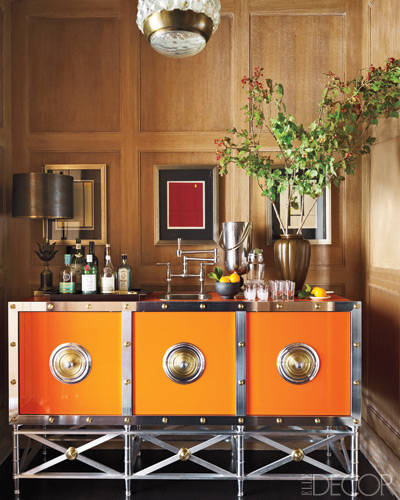 An orange metal cabinet cum bar sink in a sitting room's alcove designed by Steven Gambrel. Elle Decor; photo by Eric Piasecki.