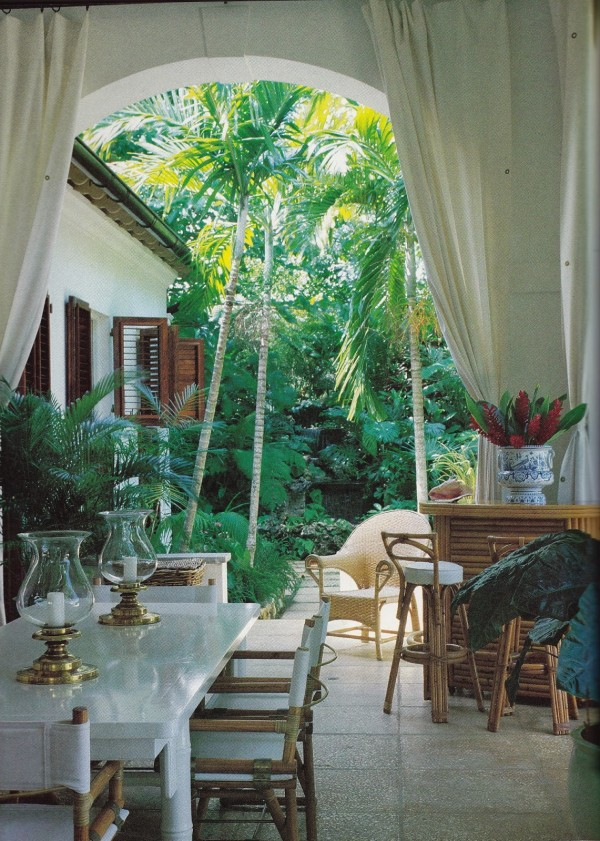 In a photo taken in 1984 of Ralph Lauren's veranda at Round Hill, Jamaica, a white lacquer bamboo dining table is surrounded by McGuire dining chairs. The bar is from the 1930's. Design by Angelo Donghia.