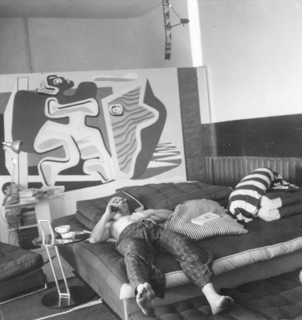 Le Corbusier lounging on the salon's bed in front of his mural. From Eileen Gray: Her Life and Work by Peter Adam.