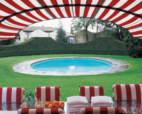 At the 15th-century Tuscan villa of fashion scion Leonardo Ferragamo, the circular pool dates from 1950, and the boxwood hedges echo the contours of the wall beyond. A boldly striped fabric covers a set of iron chairs and an awning, all designed by Francesca Garagnani and Carlo Ludovico Poccianti of Archflorence. Photo by Pieter Estersohn.