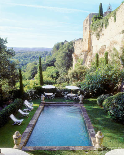 Inspired by an ancient fortress on a dramatic cliffside property in Provence's Luberon region, French decorator Michel Biehn installed a rustic, stone-edged pool embellished with ornamental urns at each corner. Photo by  Bruno Suet.