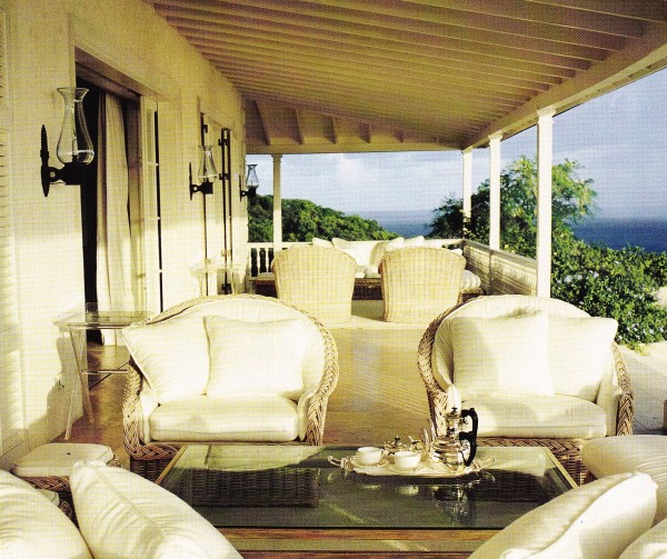 Emma Bright of Colefax & Fowler grouped wicker furniture on a plantation-style veranda in Mustique. Photo by Luke White for Architectural Digest.