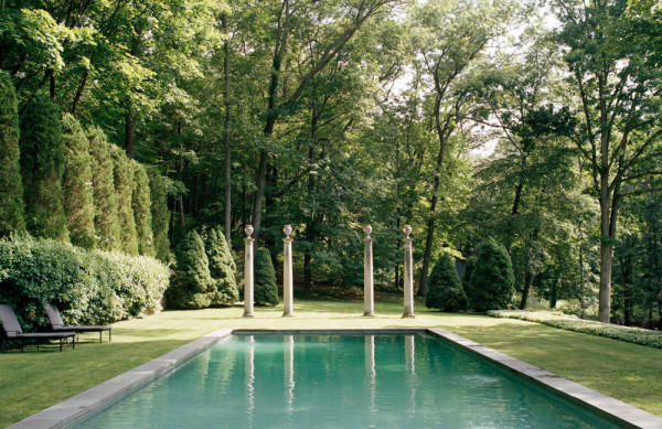 An expansive pool is set into the bucolic setting of Stephen Sills Bedford property, punctuated by classical columns at one end. Photo by François Halard for Town & Country.