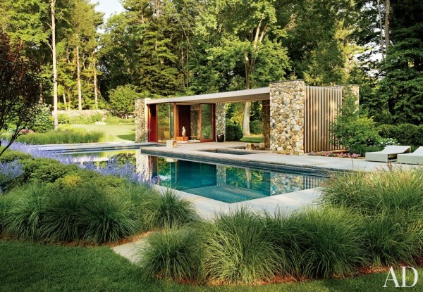 A poolhouse in Westport, Connecticut, designed by the New York City architectural firm SPaN, is distinguished by fieldstone walls and a slatted cedar pergola. Photo by Adrian Gout