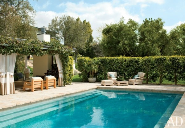 David Sutherland lounge chairs are grouped on the flagstone pool deck at actor Hank Azaria's Bel Air, California, home, decorated by Trip Haenisch. Photo by Roger Davies.