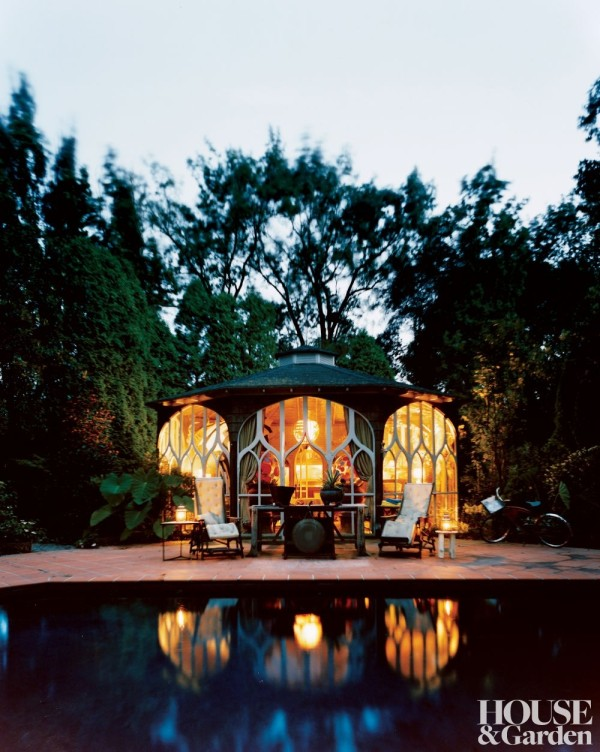 The pool pavilion of a Southampton, New York, property — lit like a lantern — serves as a guesthouse or reception area for parties. Bill Sofield arranged antique mahogany invalid chairs poolside, and an Indonesian teak table and a gong rest between them. Photo by Martyn Thompson.