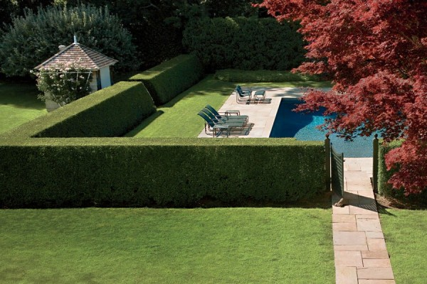 High hedges, sculpted with dramatically sloping sides, encircle a pool at a venerable Hamptons estate. Minimalist chaise longues and tables, selected by interior designer Mariette Himes Gomez, echo the clean-lined plantings. Photo by Scott Frances.