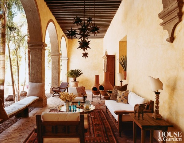 On the outdoor patio of designer Anne-Marie Midy's Mexican hacienda, traditional hacienda furniture is lightened with cream cushions. Photo by François Halard.