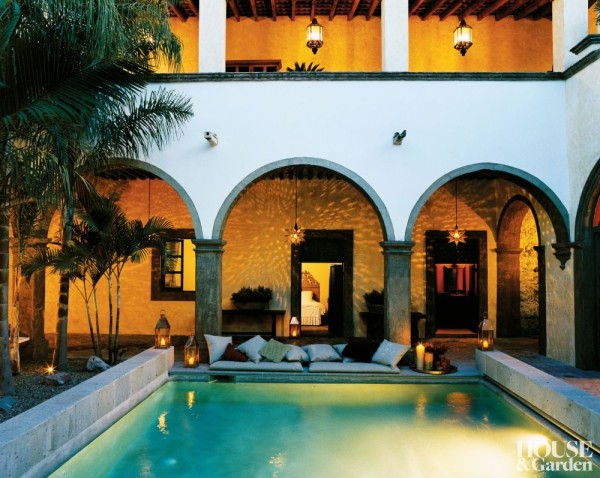 The poolside patio of Anne-Marie Midy's  Mexican hacienda is lit with copper lanterns. The hanging tin star lights are a traditional design. Photo by François Halard.