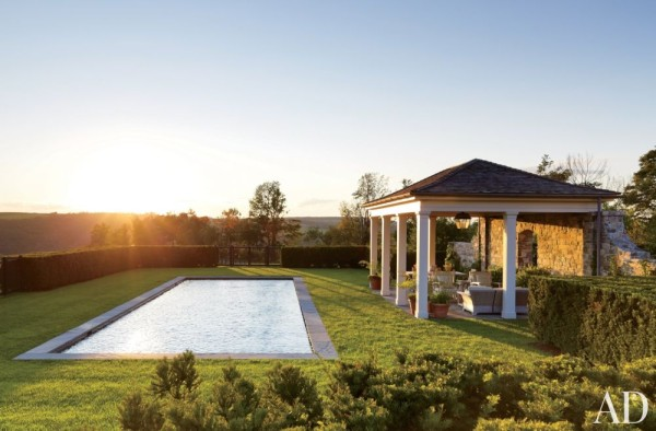 A columned cabana is situated alongside the discreet swimming pool at a Dutchess County, New York, farmhouse designed by architect Gil Schafer. Photo by Eric Piasecki.