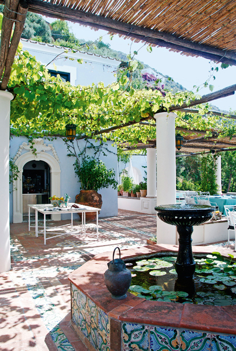 A terrace shaded by a vine-covered pergola is decorated with local Italian tiles.