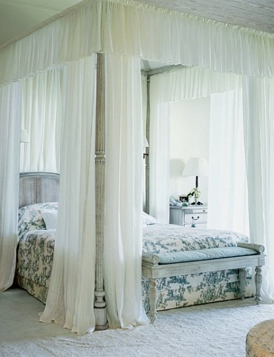 The master bedroom is a restful study in foggy gray and white. Photo by Luke White for Architectural Digest.